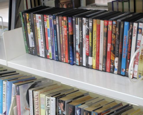 A row of DVDs is arranged neatly on a shelf.